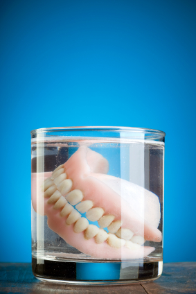 A pair of dentures floating inside of a glass jar.